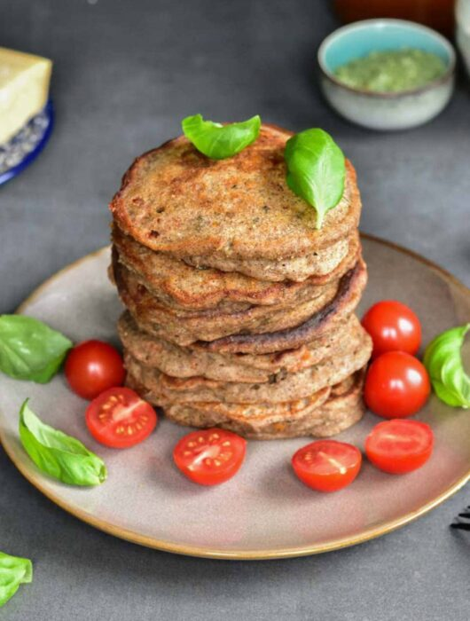 A stack of buckwheat pancakes on a brown plate with cherry tomatoes and basil leaves.