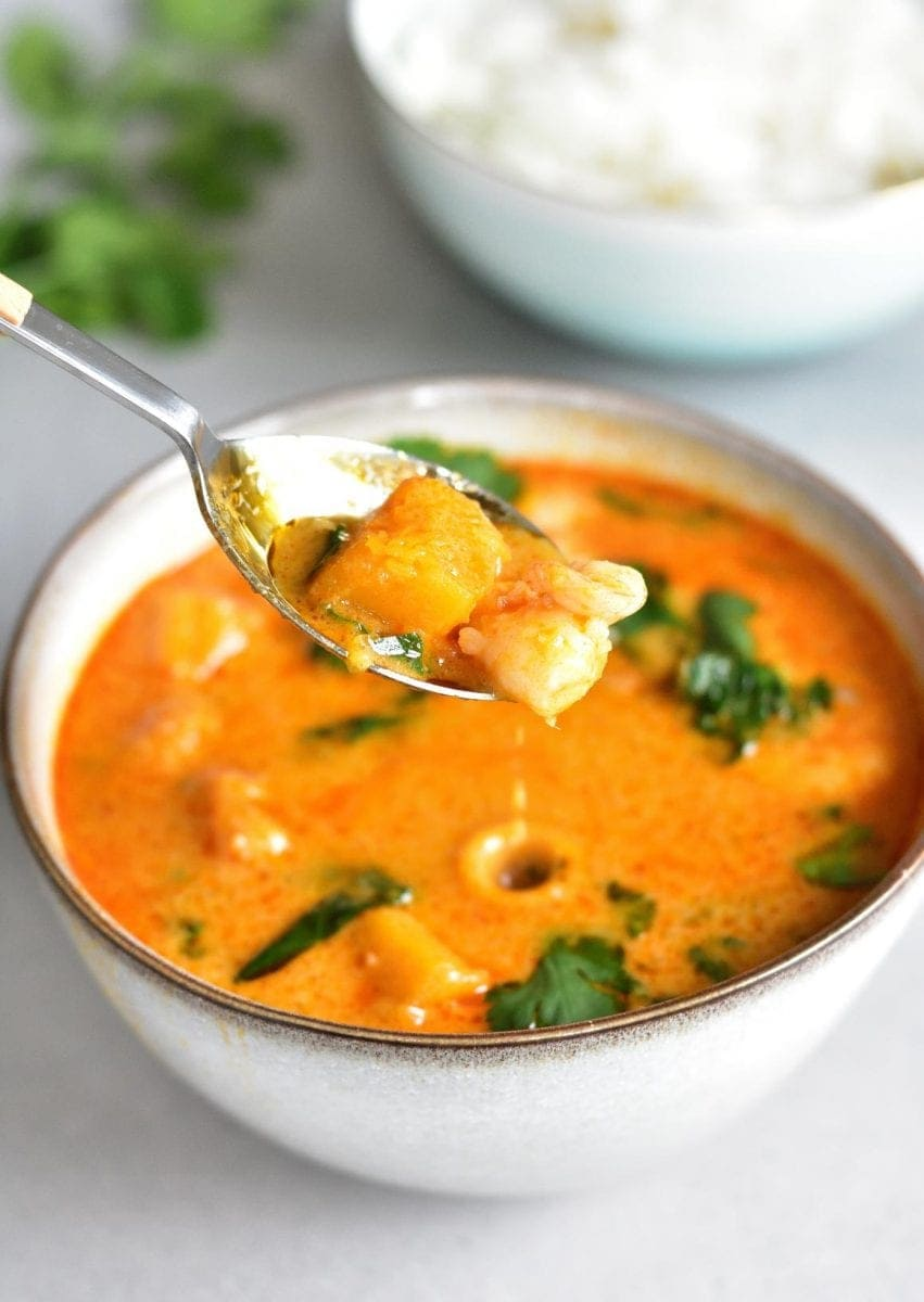 a spoon is scooping Thai red curry with shrimp and pumpkin from a bowl