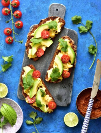 harissa, scrambled eggs and avocado toasts on a blue background