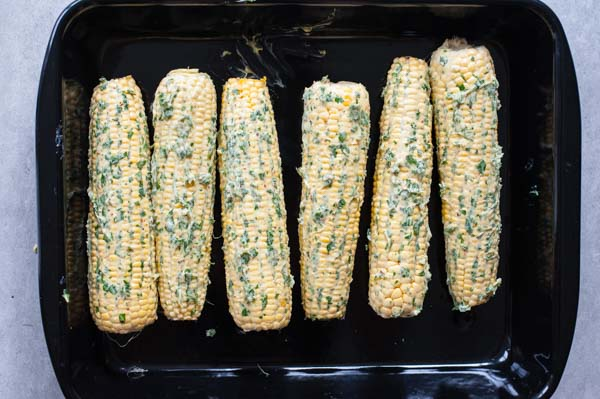 corn on the cob covered in herb and chili butter in a roasting pan