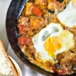 ratatouille with poached eggs in a black pan