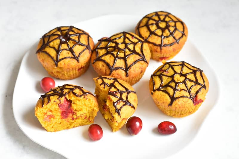 6 muffins with spider web design on top