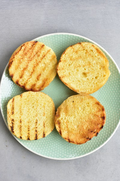 toasted brioche hamburgers buns on a green plate