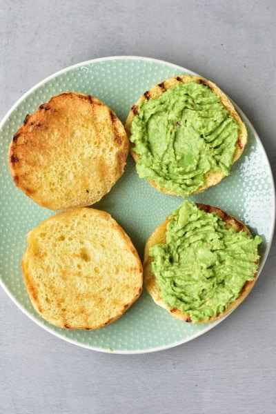toasted brioche hamburgers buns topped with smashed avocado on a green plate
