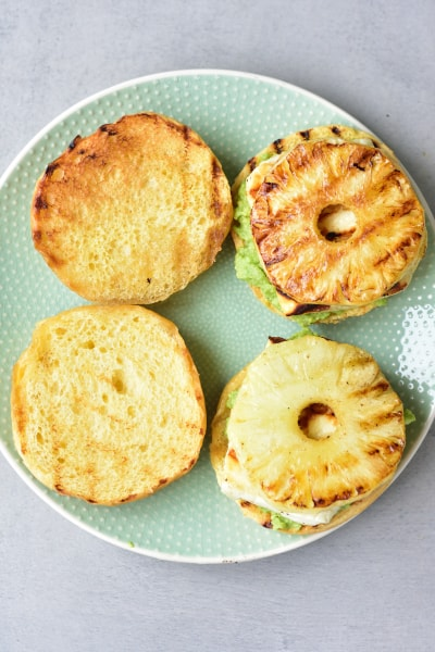 hamburger buns with avocado, grilled halloumi and pineapple on a green plate