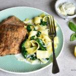 Makaron z sosem z gorgonzoli, szpinakiem i rybą na talerzu