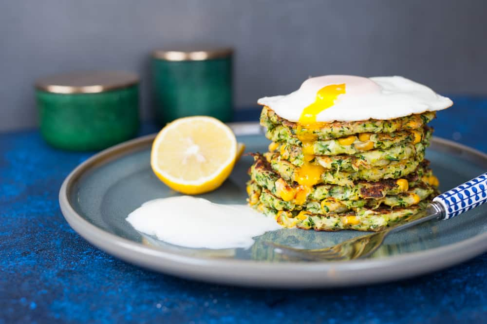 a stack of zucchini corn frittes with poached egg and yogurt