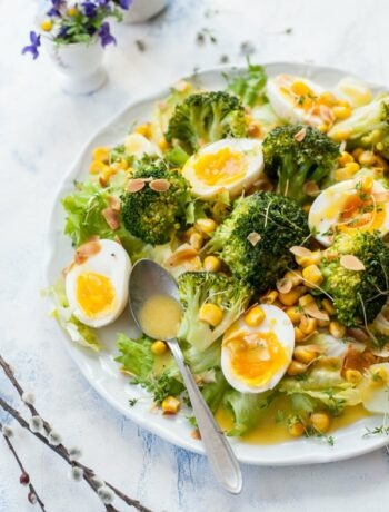 broccoli egg salad with honey mustard dressing on a white plate