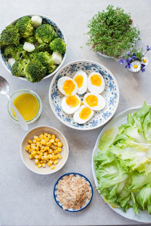 Ingredients needed to prepare broccoli egg salad with corn and honey mustard dressing on a table