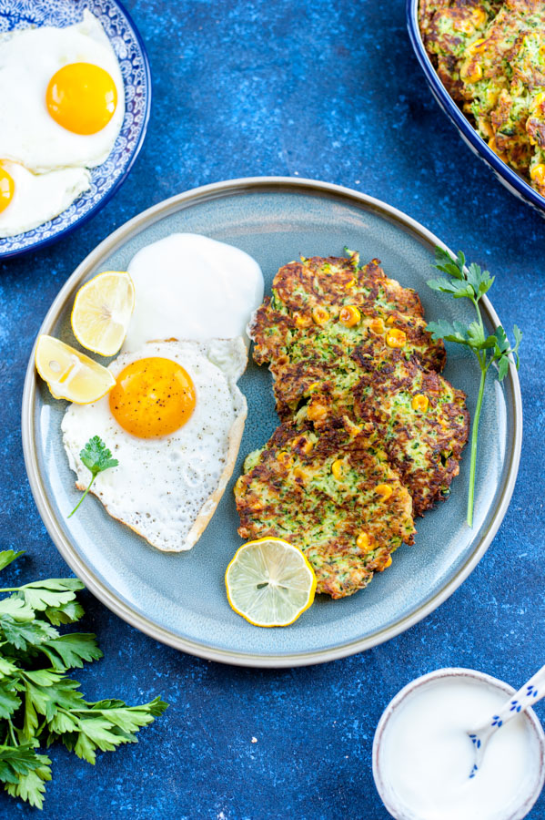 zucchini and corn fritters with fried egg on the side on a blue plate