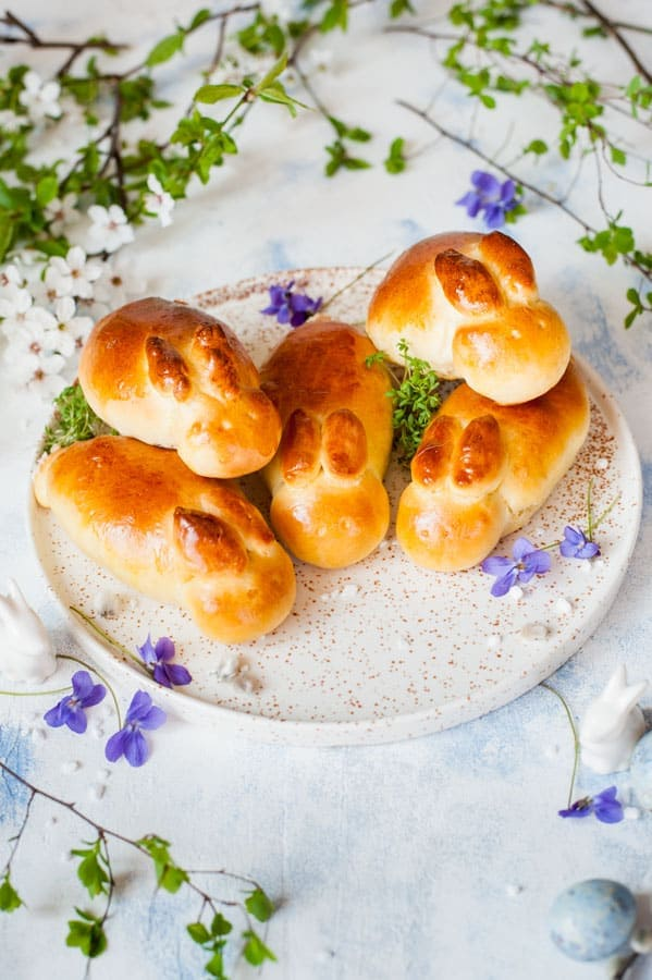 Easter bunny rolls on a white plate with lots of spring flowers in the background