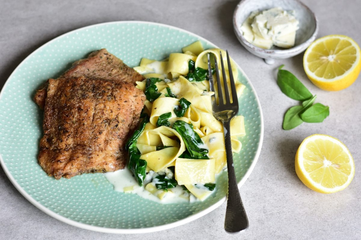 Fish with gorgonzola spinach and lemon pasta on a green plate