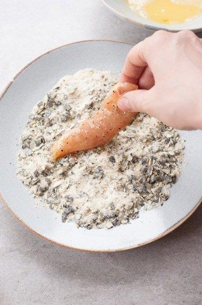 Chicken tenderloing is being coated in breadcrumbs and pumpkin seed mixture