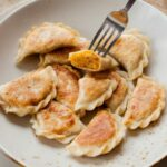 vegan pierogi with lentil and sun-dried tomato filing on a light brown plate