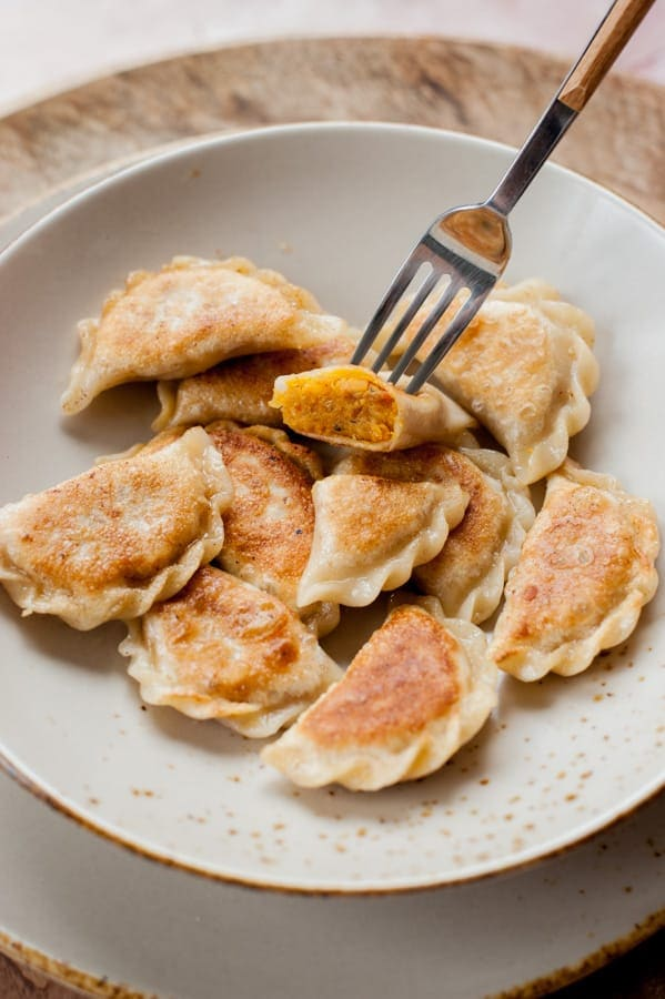 Vegan pierogi with lentil and sun-dried tomato filing on a light brown plate.