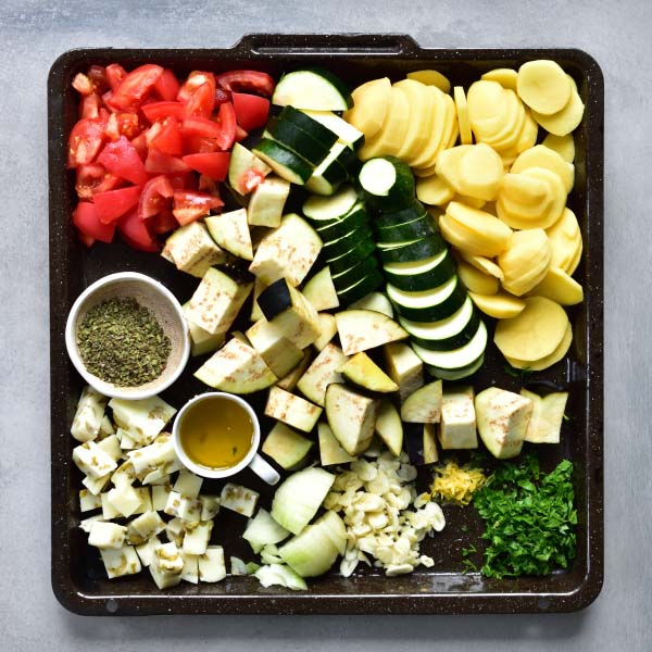 Chopped and sliced vegetables and aromatics needed to prepare briami greek style casserole on a black tray