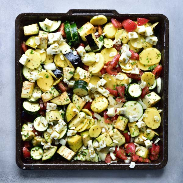 chopped vegetables and cheese mixed on a black baking tray