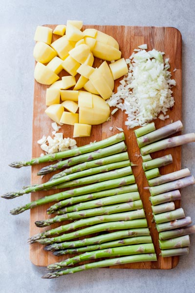 trimmed asparagus ends on a chopping board, chopped potatoes, onion and garlic