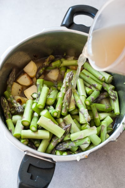 asparagus in a pot, broth is being poured in the pot