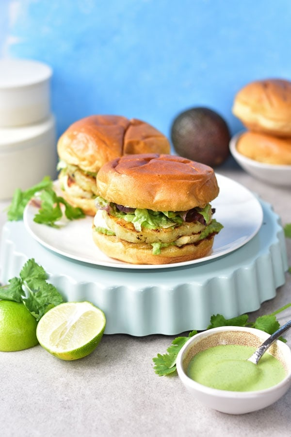 two halloumi burgers on a white plate, coriander, limes and avocado in the background
