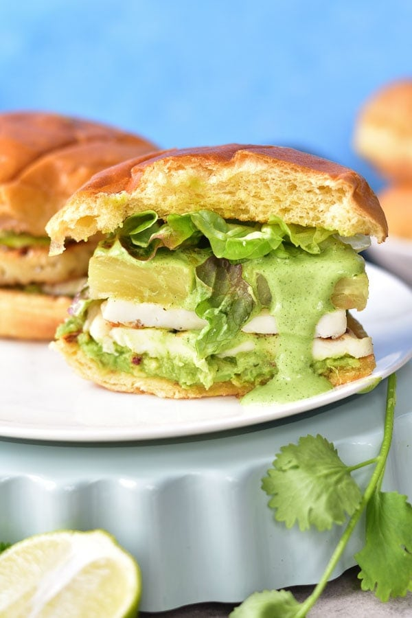 halloumi burgers with pineapple and avocado cut in half and green sauce flowing over the bun