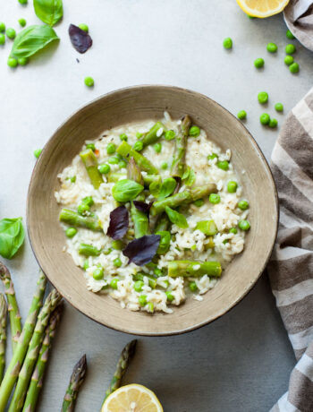 asparagus risotto with green peas in a green plate, asparagus and lemons in the background