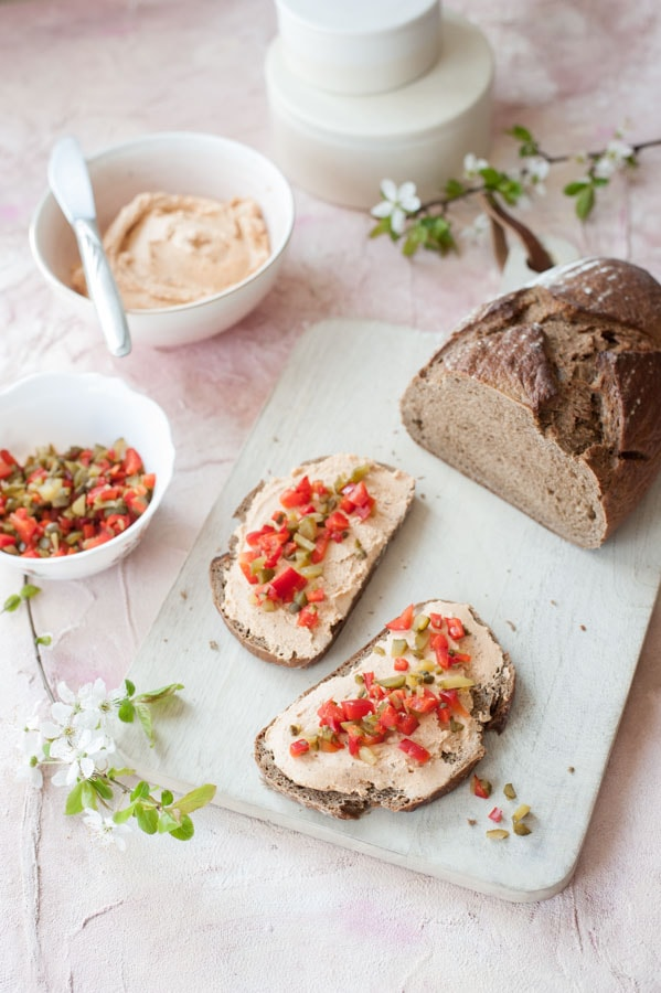 liptauer spread on a piece of bread, half the bread, bowl with topping, bowl with the spread