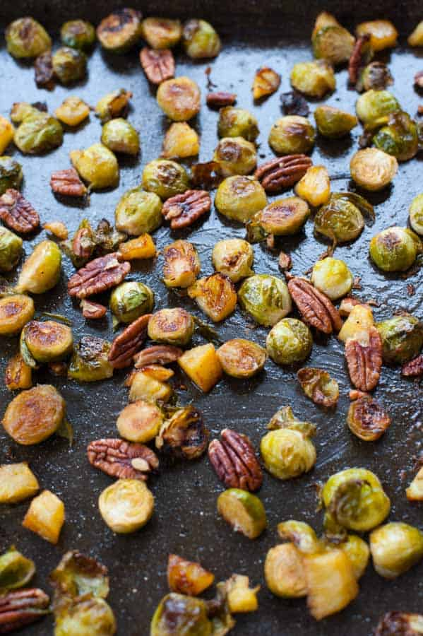 Roasted brussel sprouts with pineapple and pecans on a black baking tray
