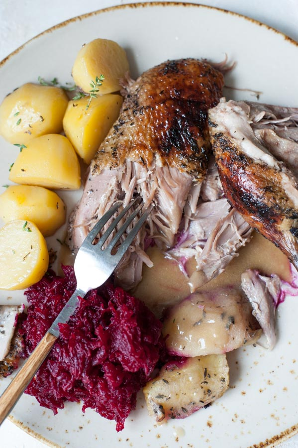 Close up on Roasted duck with apples being cut with a fork