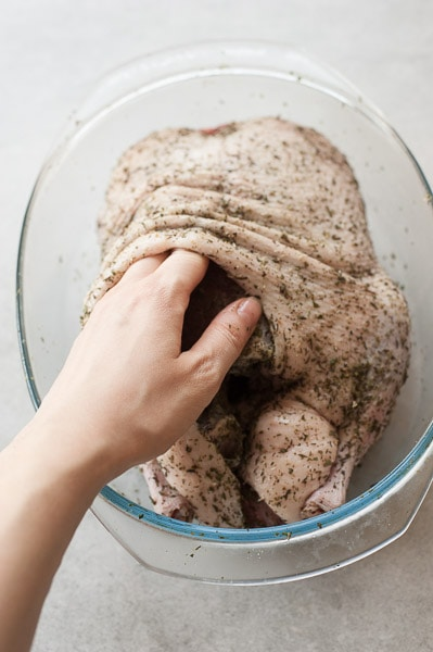 Whole duck in a baking dish is being rubbed with salt under the skin