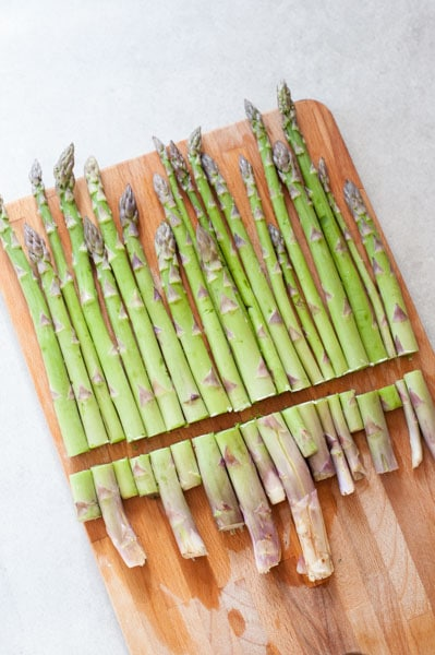 asparagus with cut off woody ends on a chopping board