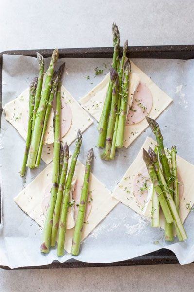 squares of puff pastry with slices of ham, cheese and asparagus on top