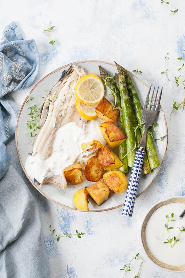 Whole roasted trout with potatoes, asparagus and thyme-garlic dip on a plate