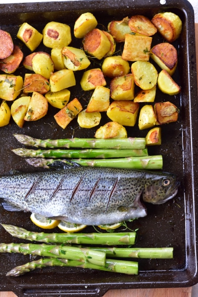 Potatoes, whole trout and asparagus on a baking tray