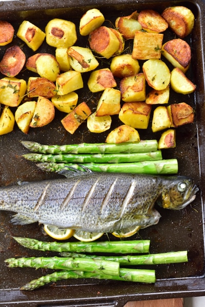 Ready whole roasted trout, potatoes and asparagus on a baking tray