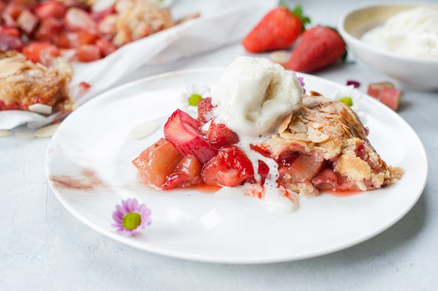 a piece of strawberry rhubarb galette on a white plate