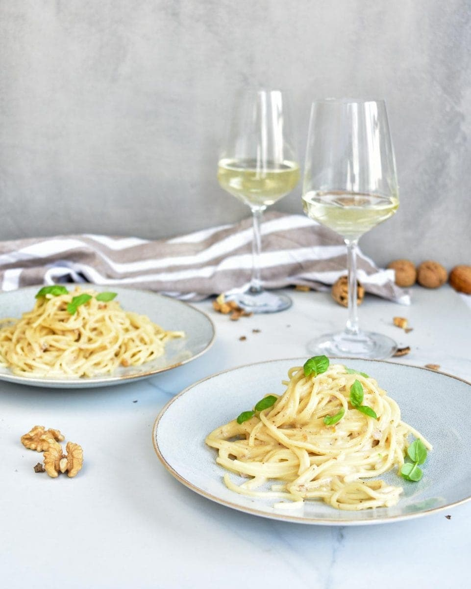 Gorgonzola walnut pasta on two blue plates, white wine in glasses on the side.