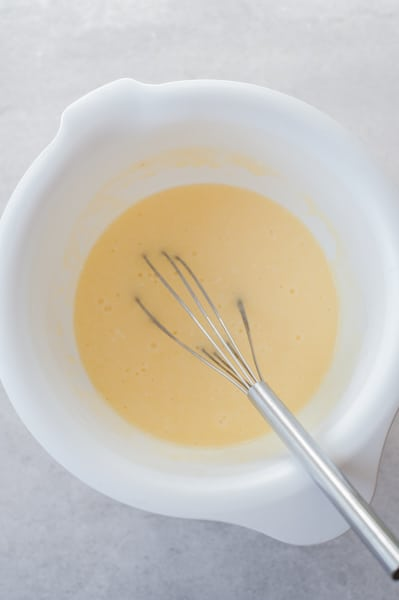 mixed wet ingredients for mango muffins in a bowl