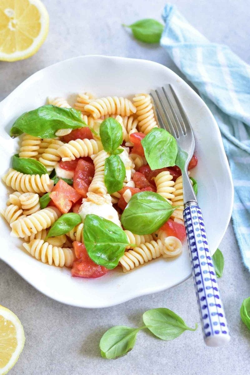 tomato mozzarella basil pasta in a white bowl
