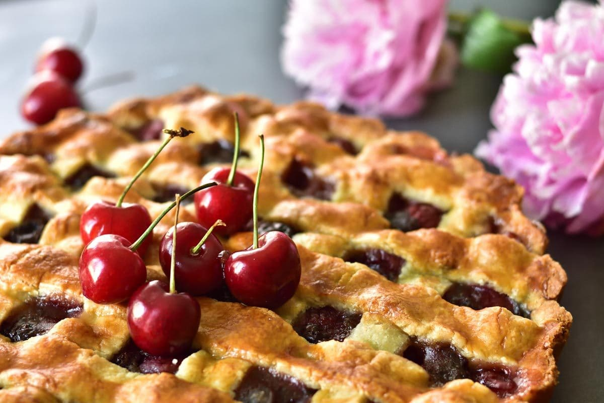 close up shot on a cherry tart. topped with fresh sweet cherries