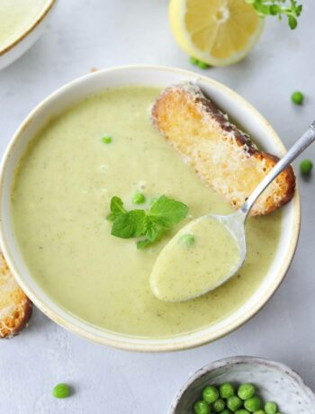white plate with zucchini soup, spoon, mint leaves and cheese toast in the middle of the soup