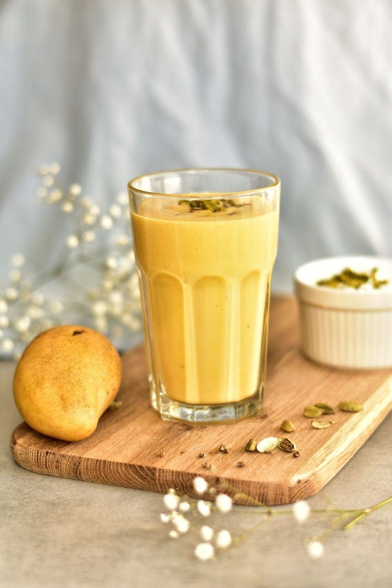 mango lassi in a glass with mango fruit and a bowl with yogurt on the side