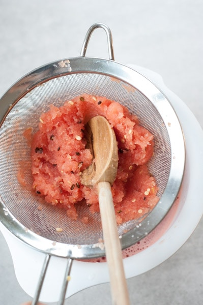 blended watermelon fleisch is being strainer through a sieve
