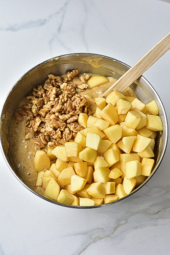 cubed apples and chopped walnuts in a metal bowl