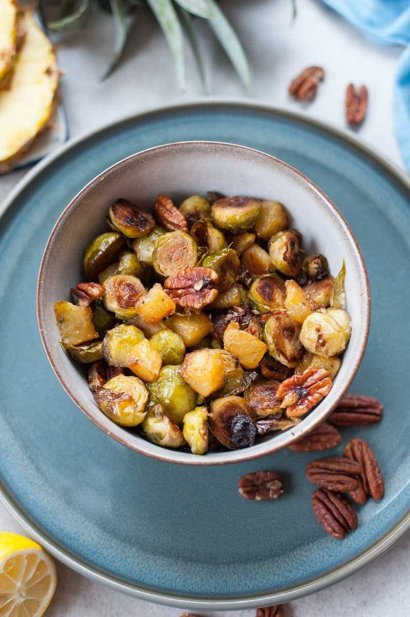close up picture of roasted brussel sprouts with pineapple and pecans in a bowl