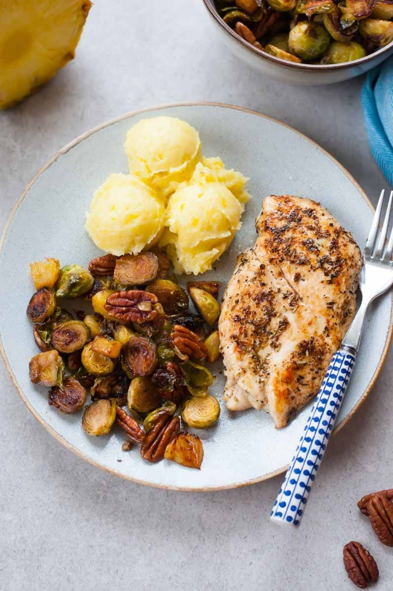roasted brussel sprouts, mashed potatoes and pan-fried chicken breast on a plate