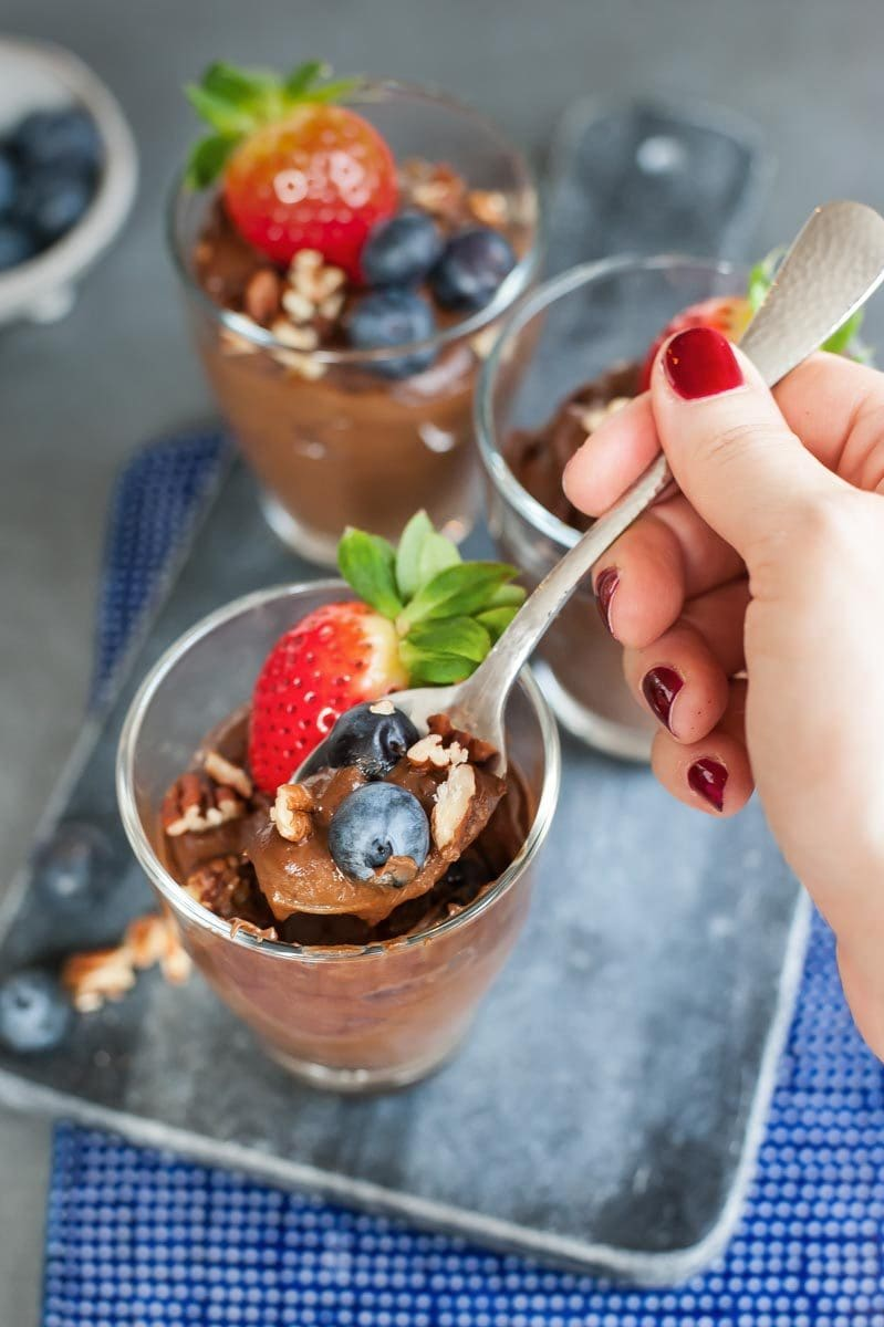 healthy chocolate pudding is being scooped out of a glass with a teaspoon