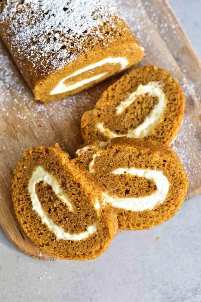 pumpkin roll with orange cream cheese, pumpkin roll slices on a wooden board