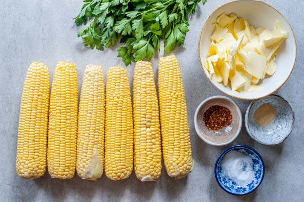 ingredients for oven roasted corn on a cob with herb and chili butter on a table