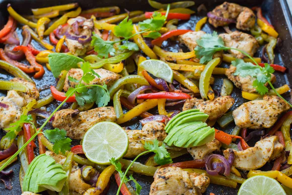 Chicken Fajitas with vegetables, avocado, coriander and limes on a sheet pan.